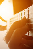 Man`s hands playing on classical guitar against a background of. Sunlight toned, warm light, contrast image. focus on neck Stock Images
