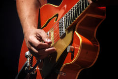 Man`s hands playing on an electric guitar on stage, entertainmen Royalty Free Stock Image