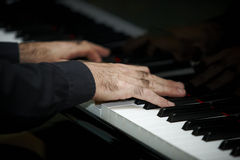 Man's hands playing piano Stock Photography