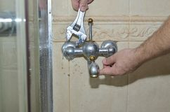 Removing old bathroom faucet. Man`s hands with a plumber wrench starting to remove an old bathroom faucet stock image