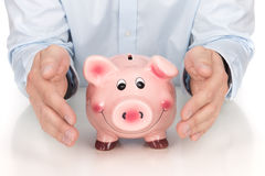 Man's hands protecting piggy bank Royalty Free Stock Image