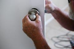 Man`s hands repairing door knob Royalty Free Stock Photography