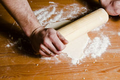 Man's hands rolled dough with wooden rolling pin on the wooden table. Royalty Free Stock Images