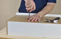Man`s hands screwing. A wood screw in a drawer backside set on working table Stock Photography
