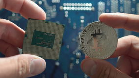 Man`s hands show silver`s Bitcoin and cpu on motherboard background. Man hands show silvers Bitcoin and cpu on motherboard background. new metal cryptocurrency stock video
