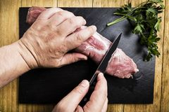 Man`s hands splitting a pork tenderloin with a knife next to some parsley branches on a black slate griddle. On a wooden table royalty free stock image