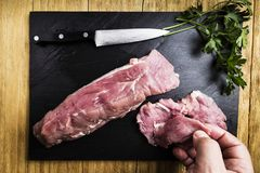 Man`s hands splitting a pork tenderloin with a knife next to some parsley branches on a black slate griddle. On a wooden table Royalty Free Stock Images