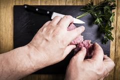 Man`s hands splitting a pork tenderloin with a knife next to some parsley branches on a black slate griddle. On a wooden table royalty free stock photos