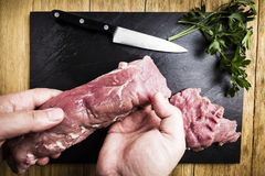 Man`s hands splitting a pork tenderloin with a knife next to some parsley branches on a black slate griddle. On a wooden table stock photos