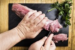 Man`s hands splitting a pork tenderloin with a knife next to some parsley branches on a black slate griddle. On a wooden table Stock Images