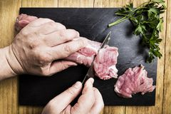 Man`s hands splitting a pork tenderloin with a knife next to some parsley branches on a black slate griddle. On a wooden table Stock Photo