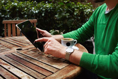 Man's hands texting message on digital tablet sitting at cafe table with plants, flare Royalty Free Stock Photography