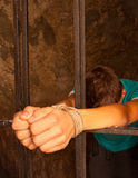 Man's hands tied with rope behind the bars Stock Photos