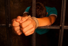 Man's hands tied with rope behind the bars Stock Photo
