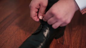 Man's hands tiyng black leather shoe stock video