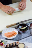 Man's hands touch sushi roll. Stock Photos