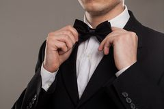 Man's hands touches bow-tie Royalty Free Stock Images