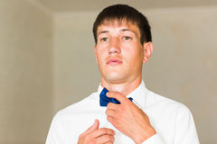 Man's hands touches bow-tie on a suit Stock Photo