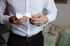 Man's hands touches bow-tie on a suit Stock Images