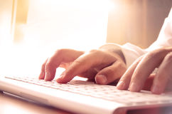 Man's hands typing on computer keyboard Stock Photo
