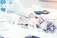 Man s hands typing at laptop, graphs. Close up of businessman s hands typing at a laptop keyboard standing on his desk in a white office. Elements of this image Royalty Free Stock Images