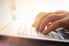 Mans hands typing on laptop keyboard stock photo
