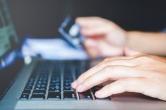 Man`s hands typing laptop keyboard and holding credit card onlin Stock Image
