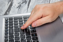 Man's hands typing laptop keyboard making online payment at home against the wooden table. On-line shopping concept Stock Photography