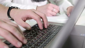 Man's hands typing on a laptop keyboard. Woman's hands writing on a paper stock video footage