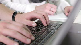Man's hands typing on a laptop keyboard. Woman's hands writing on a paper stock video
