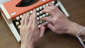 Man`s hands typing on an old red mechanical typewriter stock footage