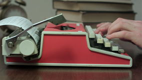 Man`s hands typing on a red mechanical typewriter stock footage