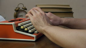 Man`s hands typing on a red retro typewriter stock video footage