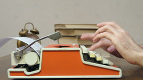 Man`s hands typing on a red retro typewriter on a table with books stock video