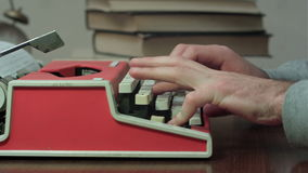 Man`s hands typing on a red typewriter. Man`s hands printing on a red typewriter. Close up shot. Professional shot on BMCC RAW with high dynamic range. You can stock footage