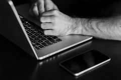 Man`s hands are typing something on the laptop. Black and white photo Stock Photography