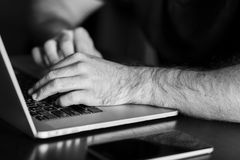 Man`s hands are typing something on the laptop. Black and white photo Stock Image