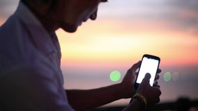 Man uses mobile smartphone near the sea at sunset beach. With blurred bokeh lights. 1920x1080. Man`s hands uses mobile smartphone near the sea at sunset beach stock footage