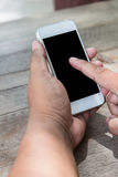 Man's hands using smart phone on wood table Stock Image