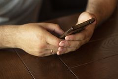 Man`s hands using smartphone. Man reading text message on cell telephone. Close-up image. Selective focus. stock photos