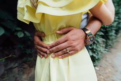 Man`s hands on the waist of a girl in yellow dress. Man holds his hands on girl`s waist. A loving couple Stock Images
