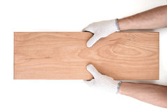 Man's hands in white cotton gloves holding wooden plank. Close up view of a man's hands in white cotton gloves holding wooden plank isolated on white background stock photo