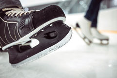 Man's hockey and women' figure skates on ice background. Closeup of blades. stock photography