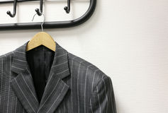 Man's jacket. Hanging on a coat hanger at a wall Royalty Free Stock Photo