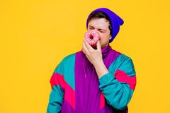 Man in 90s jacket and hat with donut on yellow background. Funny style white man in 90s jacket and hat with donut on yellow background stock photography