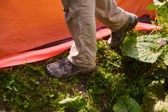 Man` s lägger benen på ryggen i smutsiga turist- kängor bredvid tältet Royaltyfria Bilder