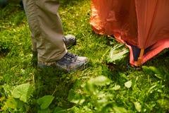 Man` s lägger benen på ryggen i smutsiga turist- kängor bredvid tältet Royaltyfri Foto
