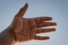 A man's left palm against sky Royalty Free Stock Photo