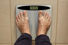 Man`s leg on a scale. royalty free stock images