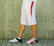 Man's legs. Man in sportswear standing near concrete wall royalty free stock photo